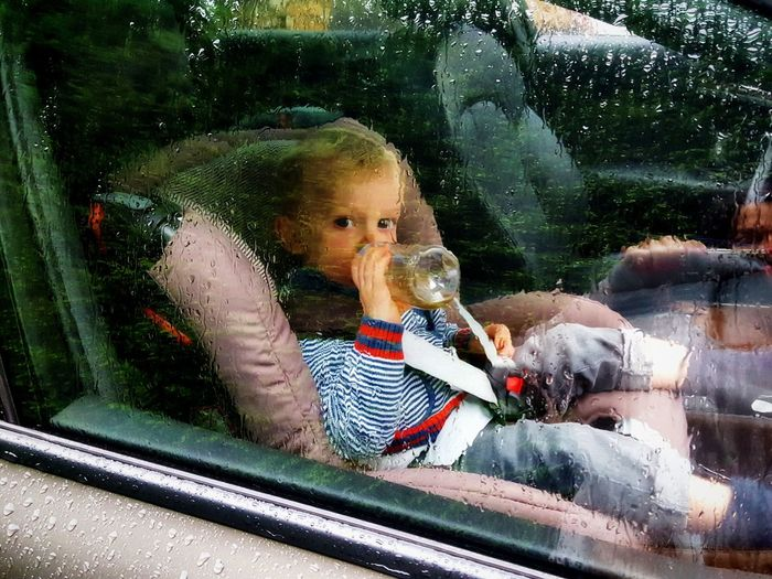 Outsider In Rain Rain Drops Sitting Waiting Boy Car Window Casual Clothing Child Seat Childhood Day Drinking Looking Through Window One Person Portrait Portrait Of A Child Protection Real People Safety Seat Seatbelt Water Window