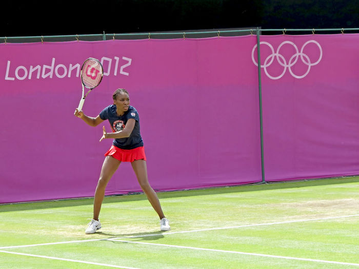 WIMBLEDON, ENGLAND - August 2nd, 2012 - Venus Williams on the practice court at the Summer Olympics in London in 2012. Olympics Tennis Venus Williams Wimbledon Adult Arms Raised Clothing Competition Copy Space Determination Effort Front View Full Length Human Arm Human Limb Leisure Activity Lifestyles One Person Pink Color Sport Standing Tennis Racket Text Women Young Adult