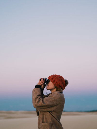 Side View Of Man Looking Through Binoculars While Standing Against Sky