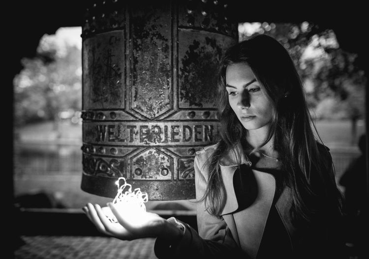 Young Woman Holding Illuminated Light Against Carving