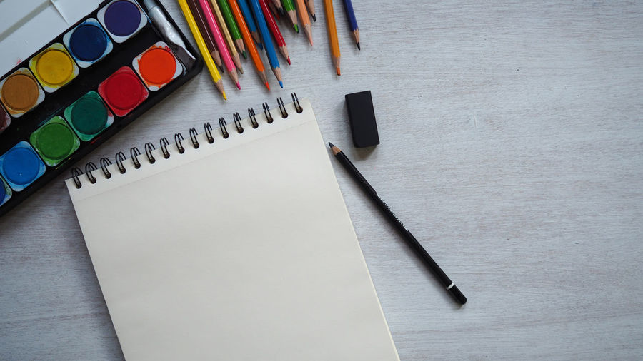 Place of work, blank white color paper page and colorful pencil on vintage wooden desk, creative designer artist concepts for business and education background Group Of Objects Wood - Material Publication Still Life Drawing Table Paper Artist Art And Craft Supplies Book Sketchbook Pen Pencil Creativity Blank Indoors  Workplace Colored Pencil Spiral Education Close-up No People Watercolor Painting High Angle View Directly Above Multi Colored Note Pad Book Pages Writing Instrument Art And Craft Equipment Spiral Notebook Indoors