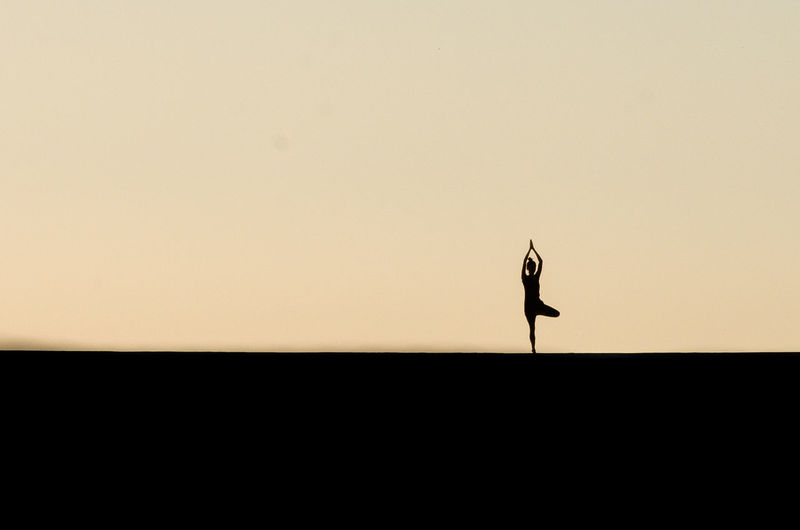 Silhouette Woman In Tree Pose On Field Against Clear Sky During Sunset