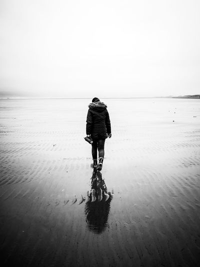 Rear view of a person walking on wet beach