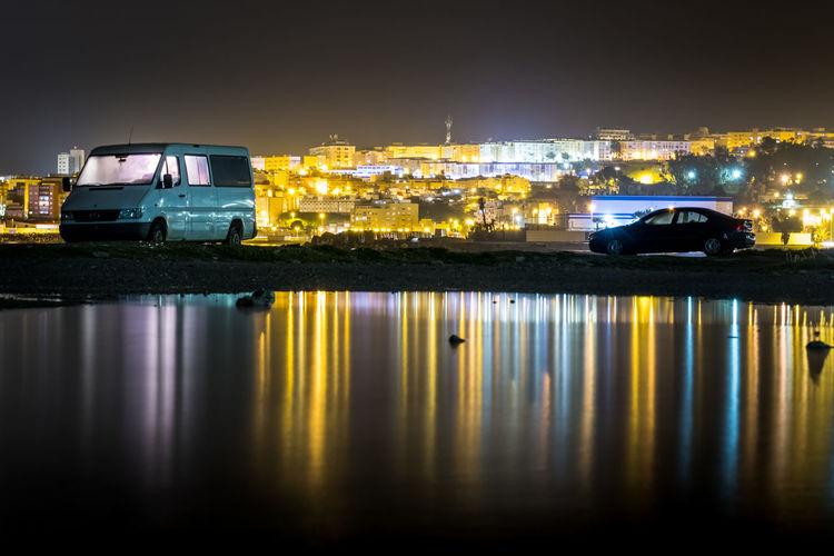Reflection of illuminated car on water at night