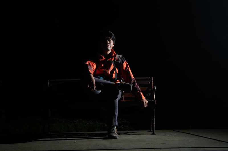 Young man standing against black background at night