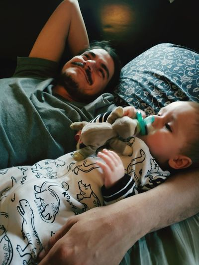 Midsection of father and son lying on bed