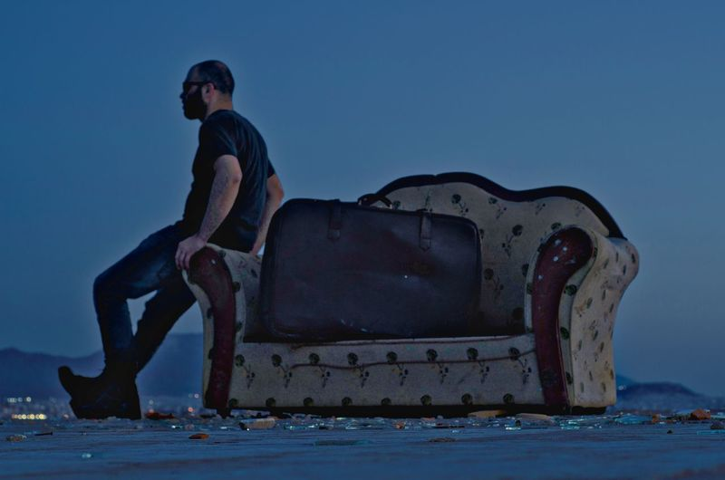 Full length of man leaning on abandoned sofa against clear sky at dusk