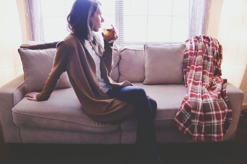 Woman drinking tea while sitting on sofa at home