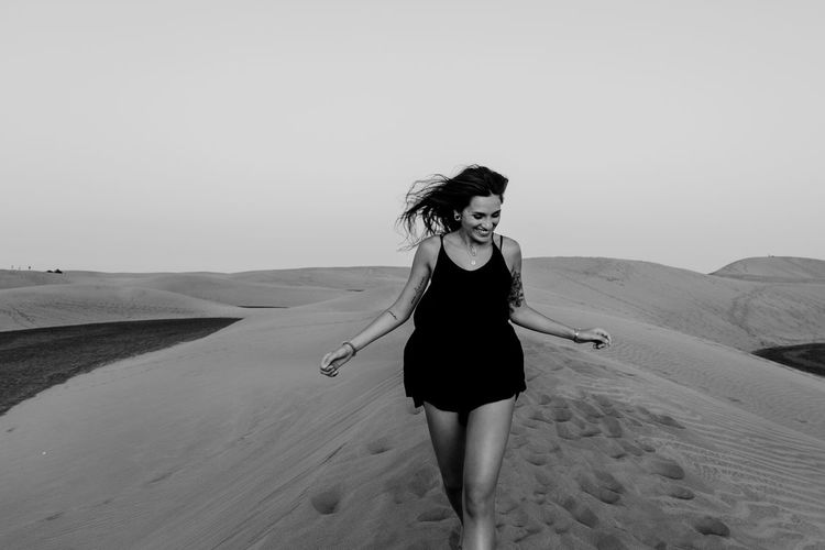 Full length of woman standing on sand dune