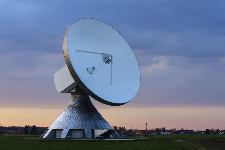 Satellite dish in city against sky