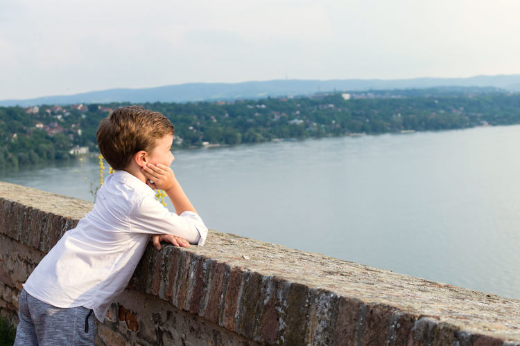 Side view of boy looking at river while leaning on retaining wall