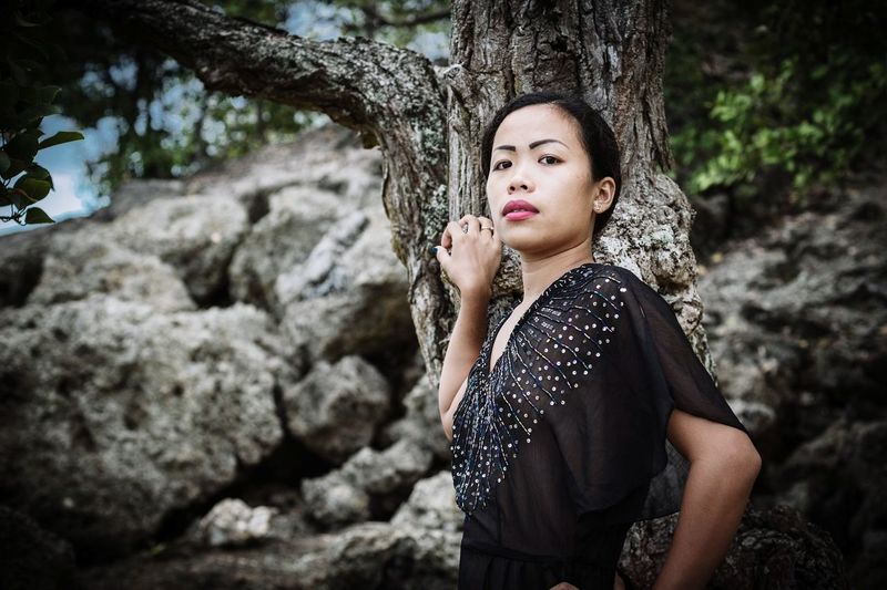 Portrait of woman on rock against tree trunk