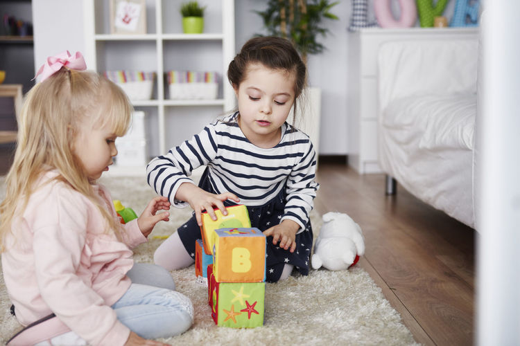 Cute girl holding toy while sitting in box at home