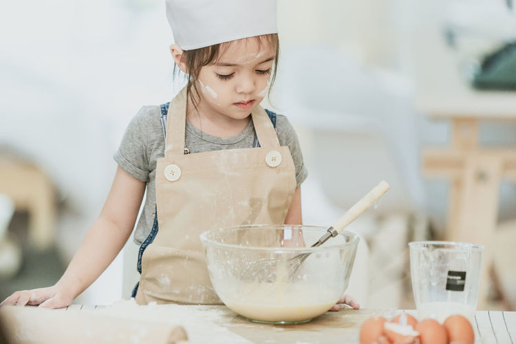 Girl holding ice cream in bowl at kitchen