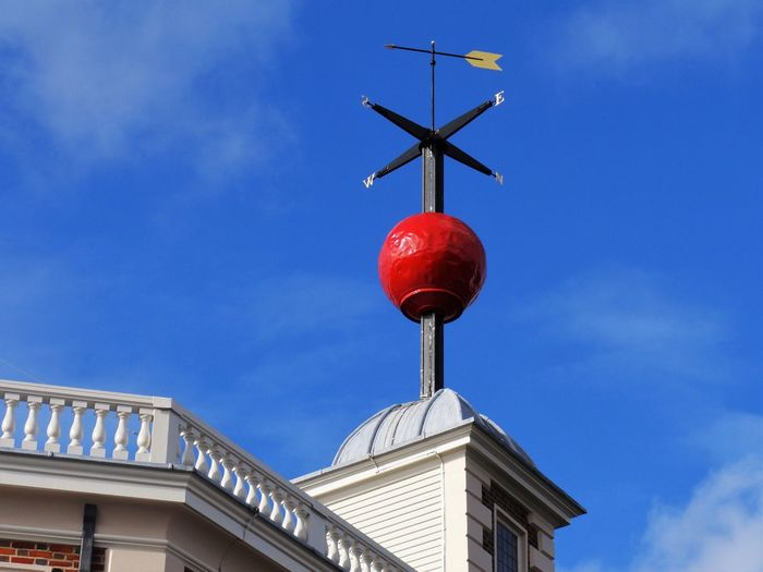 Low Angle View Of Weather Vane On Top Of Building Against Blue Sky