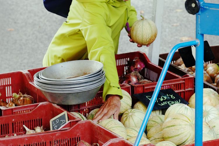 Midsection of woman choosing fruit at market stall