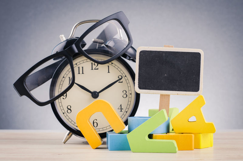 alarm clock and spectacles on wooden desk over dark background Still Life Time Indoors  Clock No People Number Alarm Clock Table Studio Shot Toy Close-up Communication Group Of Objects Large Group Of Objects Gray Text Multi Colored Metal Yellow Clock Face