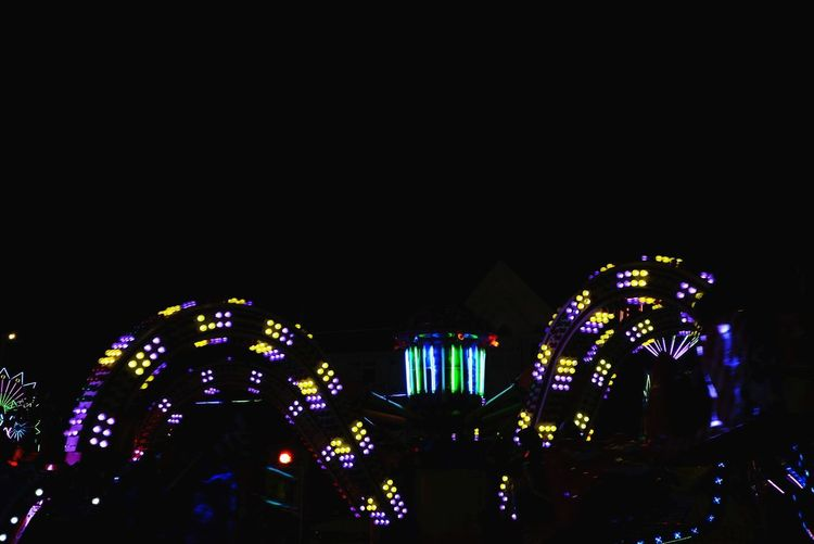 Illuminated ferris wheel by buildings against sky at night