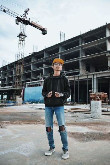 Full length portrait of young man standing at construction site