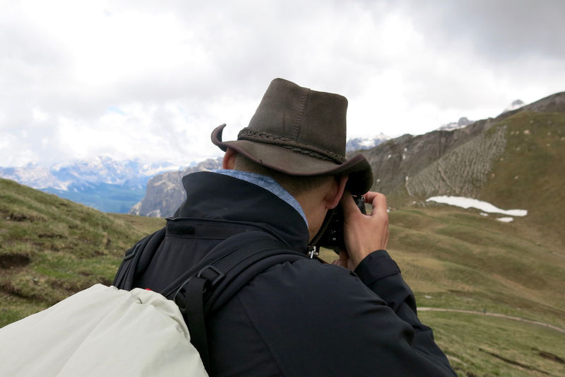 Rear view of male hiker photographing mountains against cloudy sky