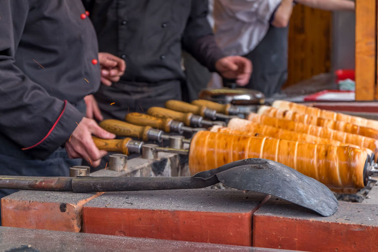 Midsection Of Men Preparing Traditional Dessert