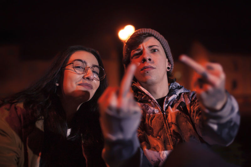 Portrait of young man showing middle fingers by friend in illuminated city at night