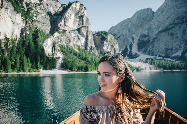 Portrait of smiling young woman in lake against mountains