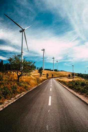 Wind turbines on road against sky