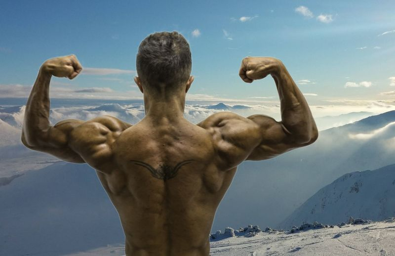 Rear view of shirtless man standing snowcapped mountain