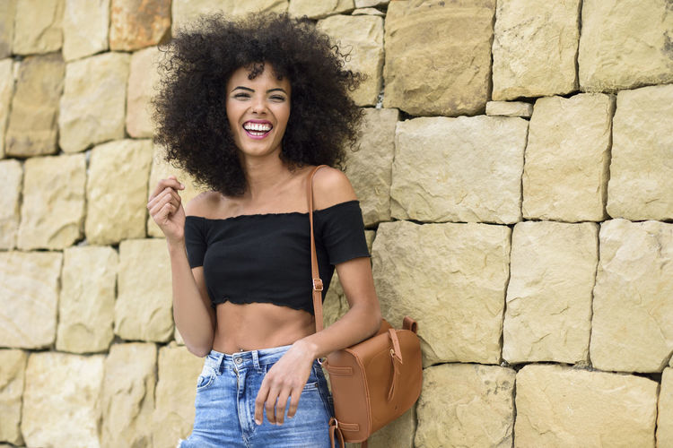 Portrait Of Happy Young Woman Standing Against Wall