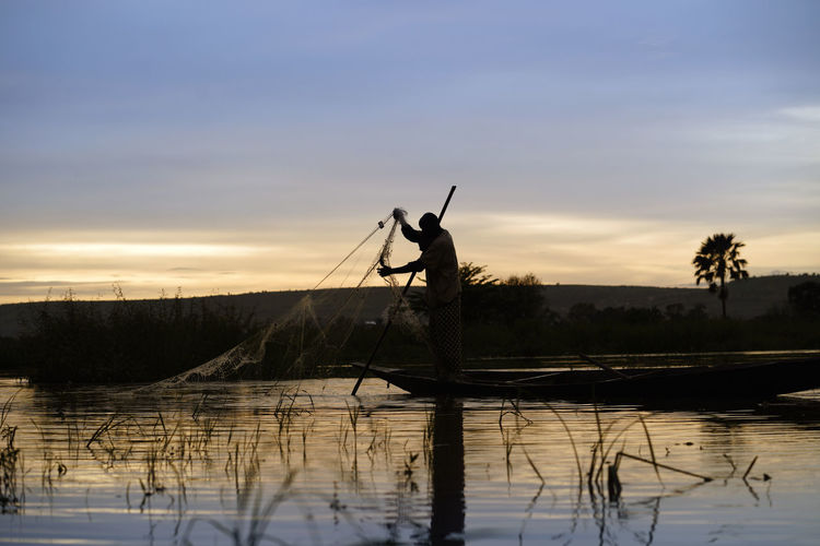 Silhouette man fishing by lake against sky during sunset