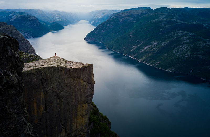 Tourist alone at Preikestolen Preikestolen Scenics - Nature Beauty In Nature Tranquil Scene Rock Mountain Rock - Object Tranquility Solid Nature High Angle View Day Non-urban Scene Idyllic Cliff Water Travel Destinations Rock Formation Outdoors Norway Landscape Lysefjord Pristine Mountain Range