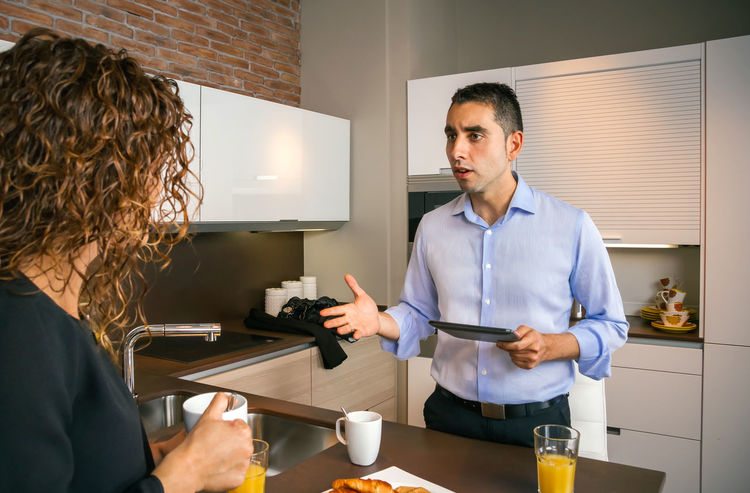 Angry young man holding electronic tablet while arguing with curly woman at breakfast in home 30s Angry Breakfast Busy Couple Discussing Food And Drink Home Horizontal Morning Orange Rush Stress Tablet Woman Worker Businessman Businesswoman Caucasian Kitchen News Problem Quarrel Technology Time