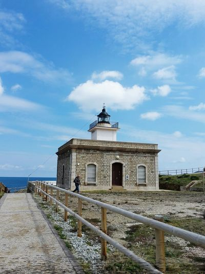 Man Walking By Lighthouse Against Sky At Costa Brava