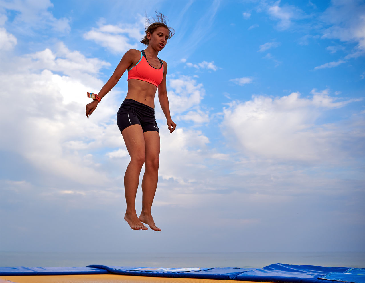 sky, cloud - sky, low angle view, full length, one person, lifestyles, mid-air, nature, outdoors, real people, day, leisure activity, blue, beauty in nature, water, young adult, jumping, sea, young women, horizon over water