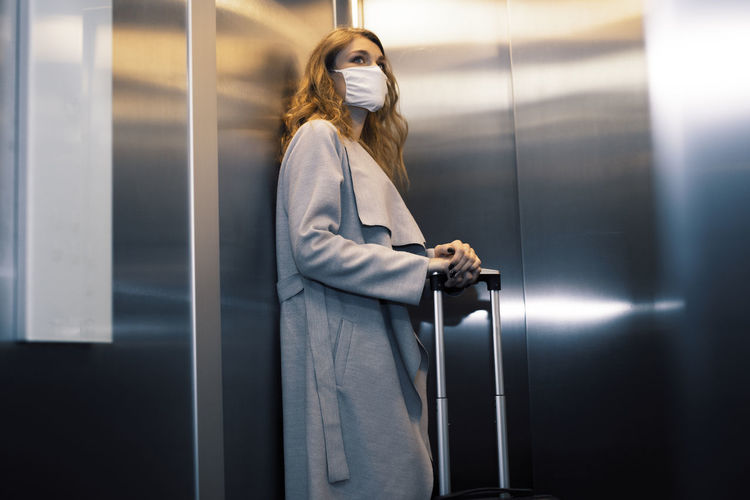 Low angle view of young woman carrying suitcase in elevator