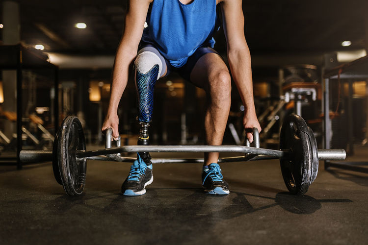 Low Section Of Man With Prosthetic Legs Exercising In Gym