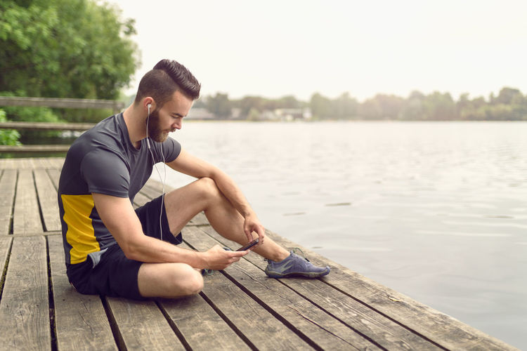 Barefoot bearded young man relaxing on a deck Athlete Bare Tree Barefoot Beard Bearded Communication Deck Fit Fitness Landscape Lifestyle Listening To Music Male Man One Person Outdoors Park Sea Smartphone Sport Water Wooden Young