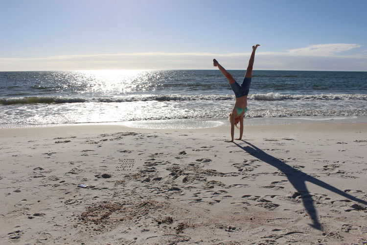 Woman doing cartwheel on sand at beach