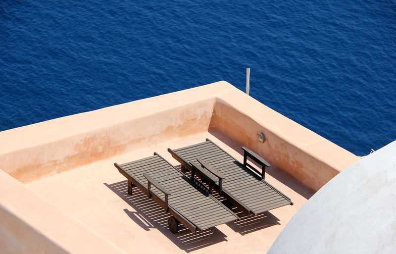 Sunbeds - Santorini Art Deco Alone Blue Day Elevated View Greece Greek Islands No People Ocean Outdoors Patio Peaceful Peaceful View Relaxing Rippled Santorini Sun Sunbeds Sunbeds On Patio Tranquility Water Wooden Two Is Better Than One