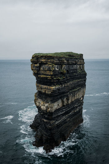 View of rock formation in sea against sky