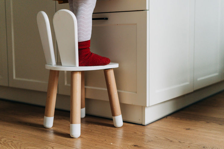 Low section of girl standing on chair at home