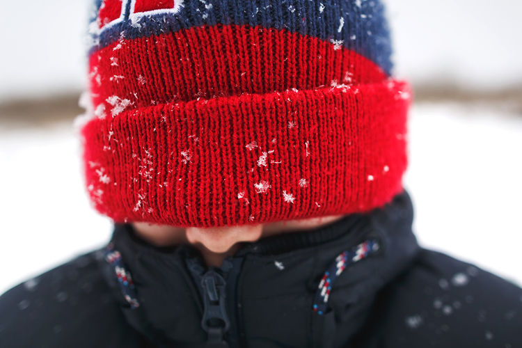 Close-up portrait of man wearing red hat in snow