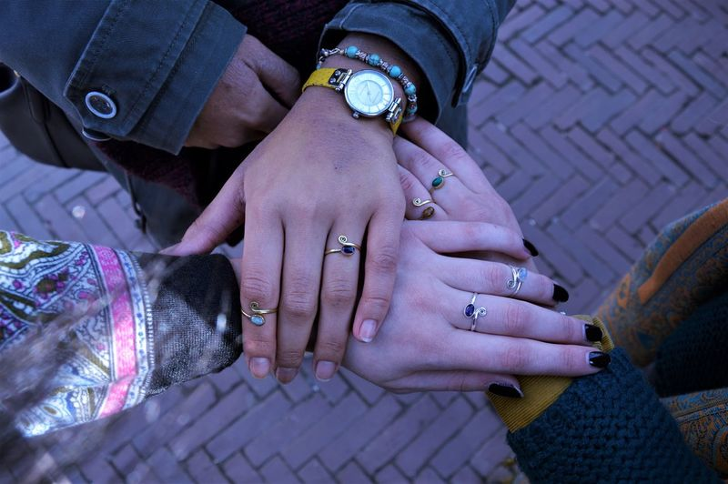 Directly above shot of friends wearing finger rings while stacking hands on street
