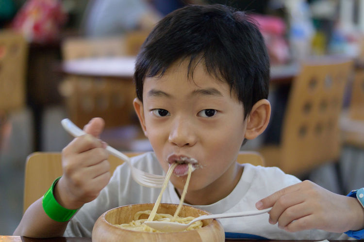 Portrait of boy eating noodles at restaurant