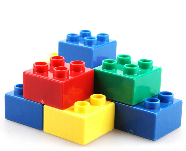 Stack of multi colored toy blocks on white background