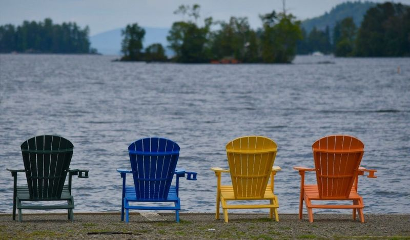 Enjoying lake life in a colorful way🌞 Chair Nature Water Beach Sea Sand Day Outdoors No People Tranquil Scene Seat Table Tranquility Outdoor Chair Folding Chair Focus On Foreground Summer Relaxation Beauty In Nature Adirondack Chairs Colorful Lake View Mountain Range Summer Memories 🌄