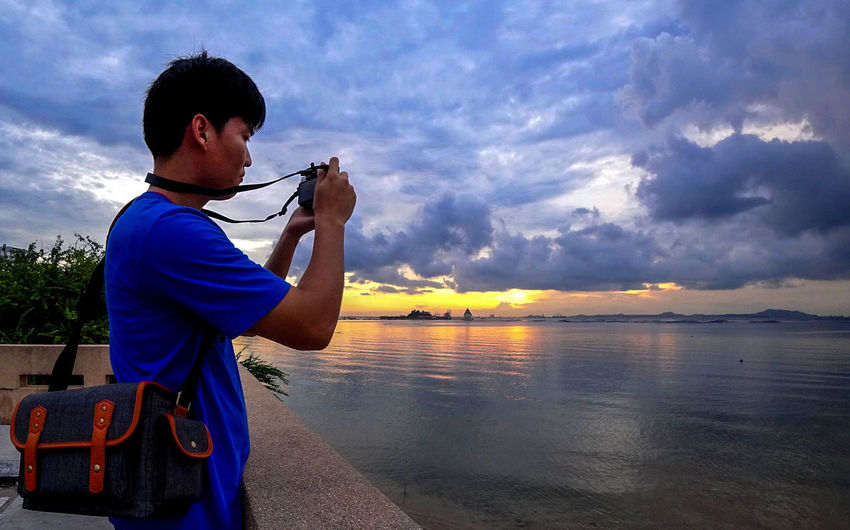 Side view of man photographing by sea against cloudy sky