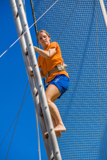 Low angle view of woman by rope against blue sky