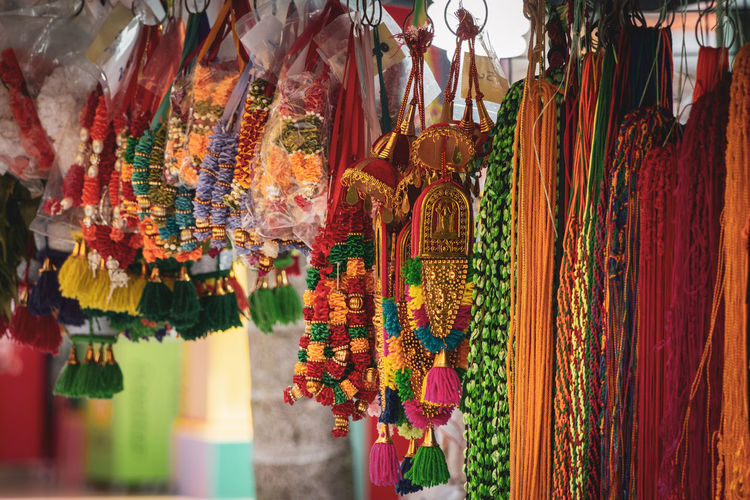 Multi colored decoration and floral garlands hanging for sale in market